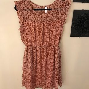 Pink ruffled summer dress with black pattern.